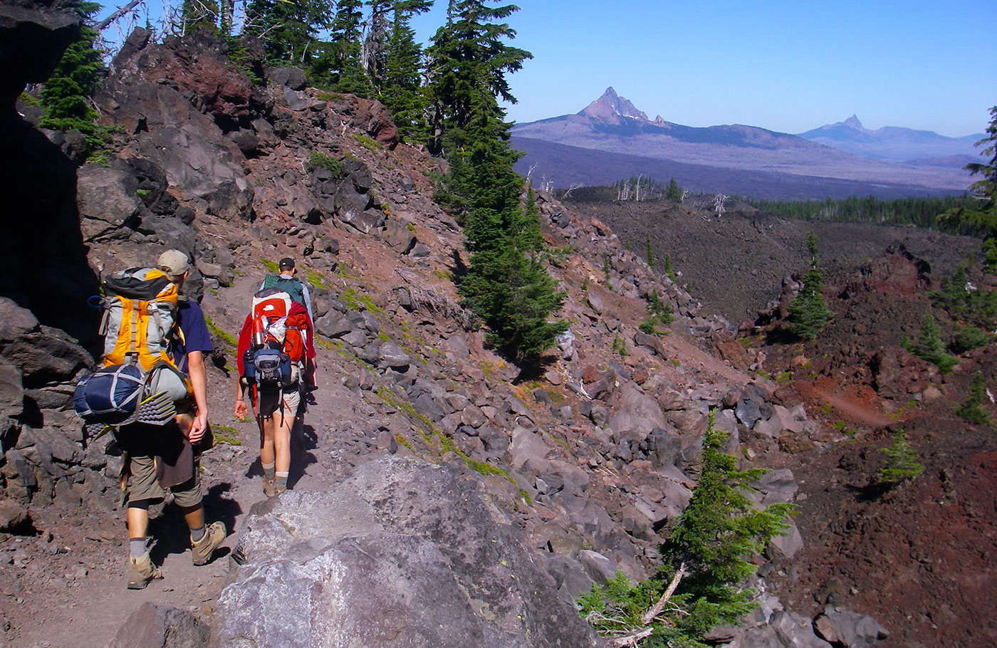 Three students backpacking on a rugged trail in the Sisters Wilderness.