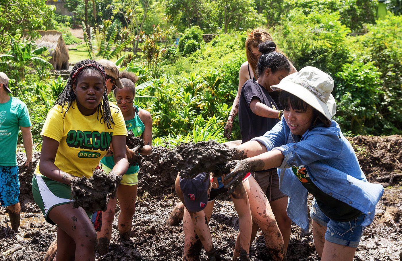 Students knee deep in mud pulling out roots from invasive plant species.