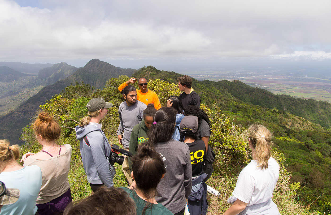 A group of students checking out the view from the top of a green mountain in Hawaii.