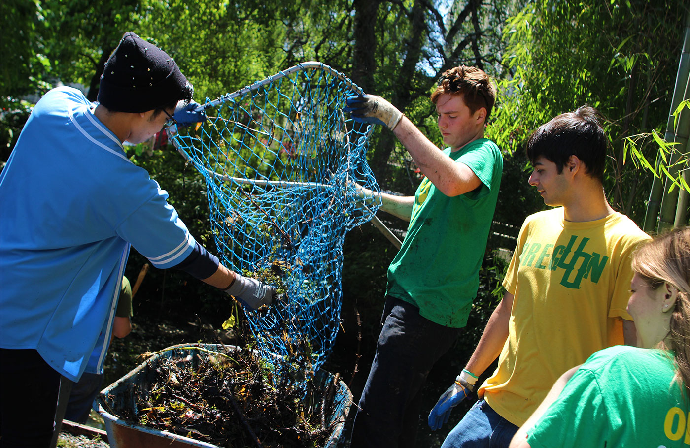 Four students removing items from a net as they clean up the nearby canal.