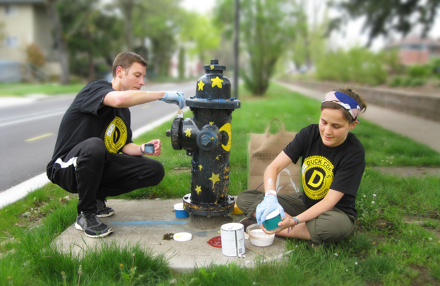 Two students painting a fire hydrant wearing Duck Corps t-shirts.
