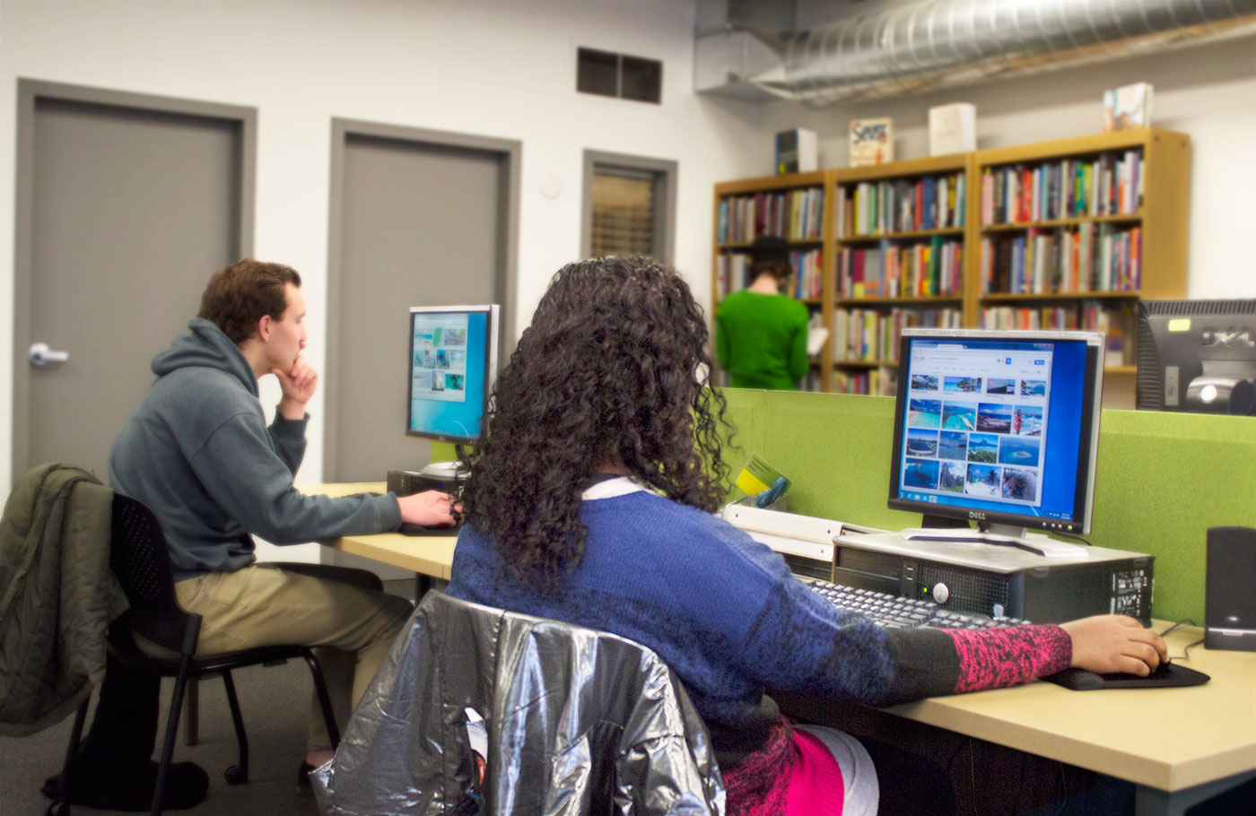 Two students sitting at the community computers inside the Holden Center while someone looks for a book in the background.