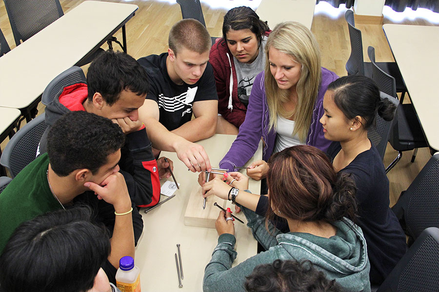 Students working together to build a house out of nails.