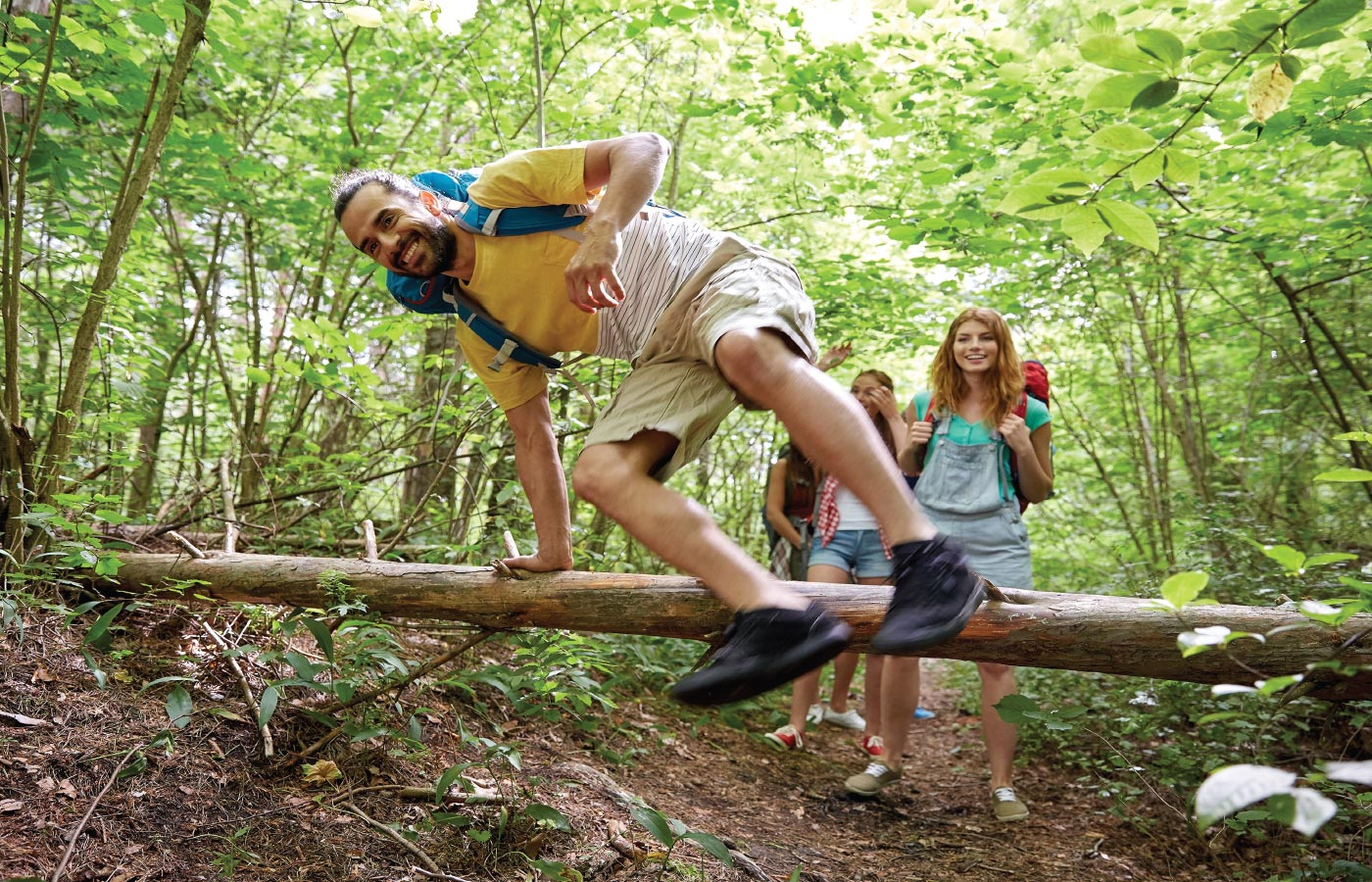 Students hiking and jumping over a log