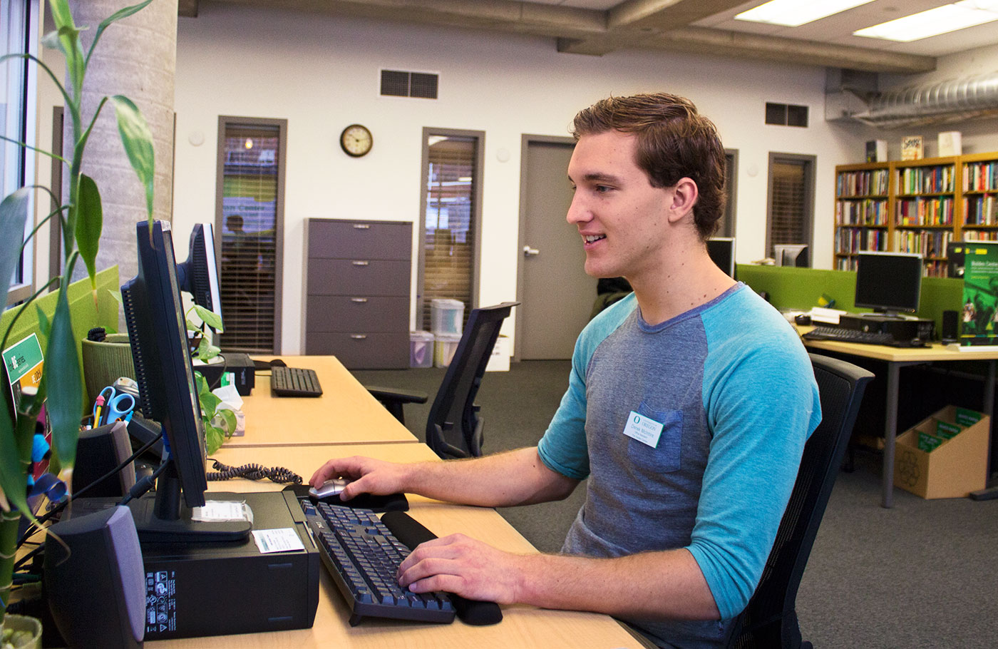 A student employee working on a computer in the Holden Center.