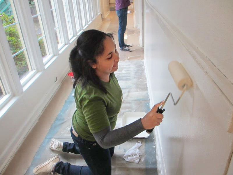 A couple students painting a hallway.